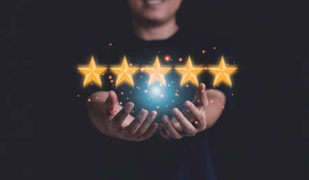 Businessman holding yellow stars on hand for customer satisfaction and product service evaluation concept.
