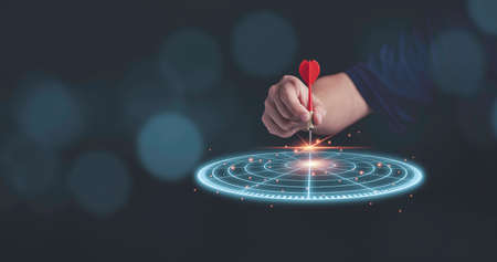 Businessman throwing red arrow dart to virtual target dart board. Setup objectives and target for business investment concept. Zdjęcie Seryjne