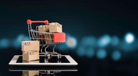 Shipping paper boxes inside Red shopping cart trolley on tablet with black and blue bokeh background and copy space , Online shopping and e-commerce concept. Zdjęcie Seryjne