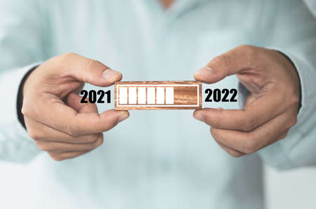 Businessman holding wooden cube block with loading progress bar for New Year's Eve and changing year 2021 to 2022. Zdjęcie Seryjne