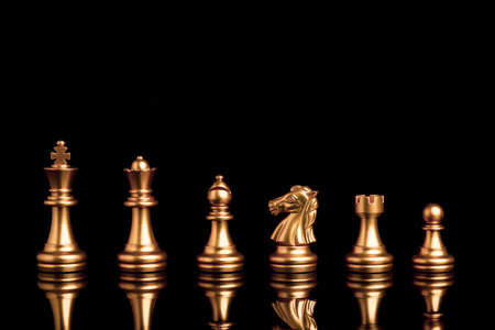 Golden chess include king queen horse ship and pawn on black background with reflection.
