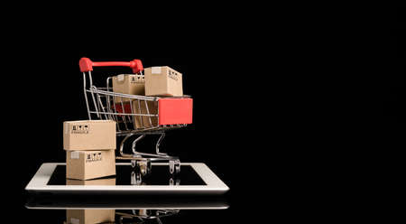 Shipping paper boxes inside Red shopping cart trolley on tablet with black background and copy space , Online shopping and e-commerce concept.