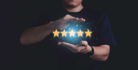 Businessman hand protect five yellow stars with blue glowing light , Customer evaluation and client satisfaction for product and service concept.