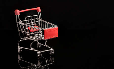 Closeup red shopping trolley cart with reflection on black background , commerce and shopping concept. Zdjęcie Seryjne