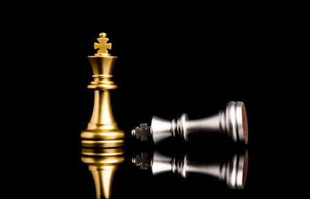 Golden king chess standing and silver king chess falling for the winner , Business competitor and strategy concept.