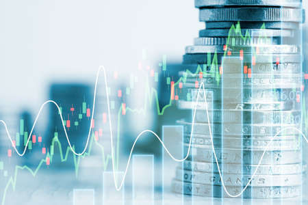 Double exposure of coins stacking with investment graph chart and cityscape. It is symbol of stock value investment concept. Zdjęcie Seryjne