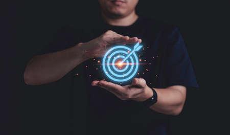 Businessman holding virtual blue dartboard with arrow ,Business Achievement objective target concept. Zdjęcie Seryjne