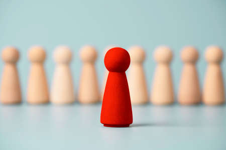 Red wooden figure standing in front of others figures on blue background, Leadership and management concept.