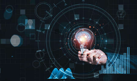 Businessman holding lightbulb with virtual brain and infographic, reative thinking ideas and innovation concept.