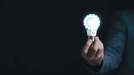 Businessman holding blue mechanical gear with virtual light bulb for creative thinking idea and innovation concept.