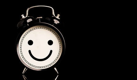 Smiley face inside of alarm clock on black background and copy space, happiness and mindset concept. Zdjęcie Seryjne