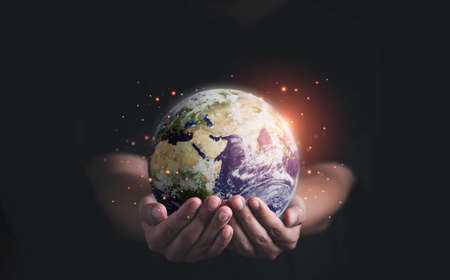 Man holding planet by two hands for earth day and saving energy environment concept