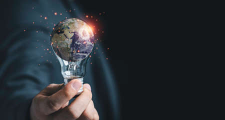 Businessman holding lightbulb with Earth for earth day and saving energy environment concept ,