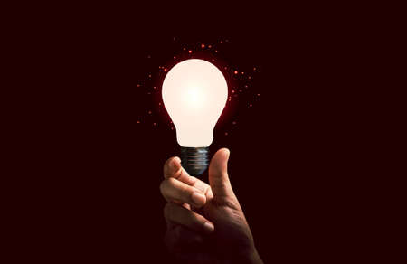 Businessman holding glowing lightbulb for creative thinking ideas and innovation concept.