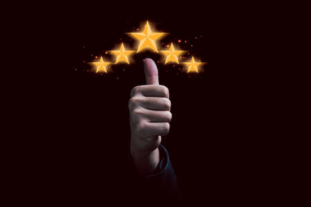 Hand and thumb rise up with five golden stars for client excellent rating and customer evaluation of product service concept.