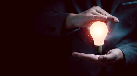 Businessman gesture protecting glowing lightbulb with copy space for creative thinking idea and problem solving concept.