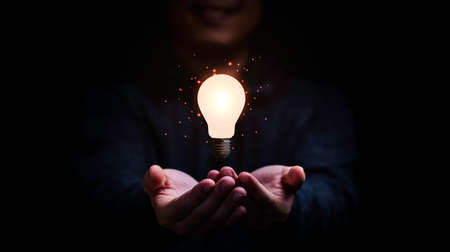 Businessman holding glowing lightbulb for creative thinking and problem solving concept.