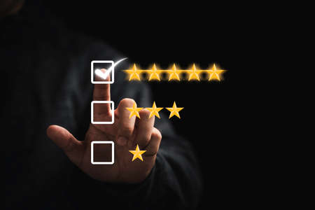 Businessman touching button to select five stars for the best excellent evaluation of customer satisfaction of product and service concept.