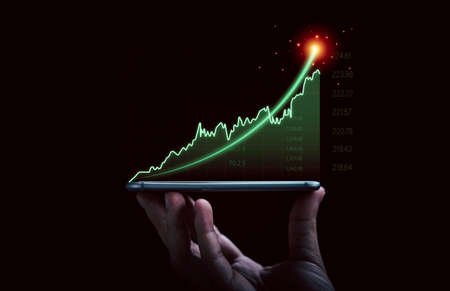 Businessman hand holding smartphone with increasing virtual investment graph and chart for stock market analysis trend and technical by trader concept.