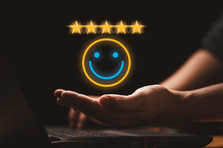 Businessman holding virtual smiley face with five stars and using computer laptop for online evaluation product and service , customer satisfaction concept. Banque d'images