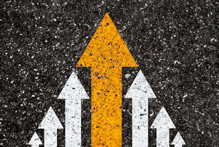 Yellow big arrow move leading from small white arrow on road asphalt for leadership concept. Banque d'images
