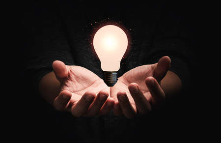 Businessman holding lightbulb glowing with connection line for creative thinking ideas and innovation concept.