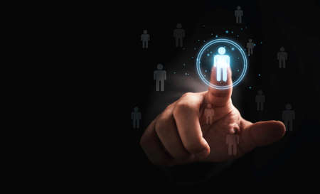 Businessman touching to virtual human icon for focus customer group or human recruitment and development concept. Banque d'images