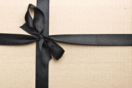 Black satin ribbon on cardboard background