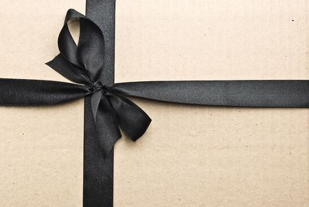 black ribbon bow:   Black satin ribbon on cardboard background