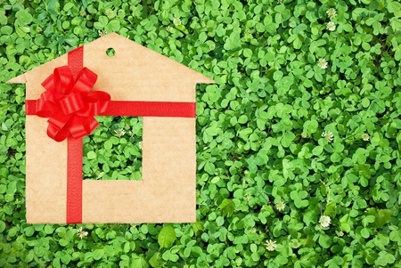 Cardboard house with a red bow on a background of green grass photo