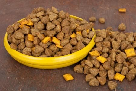 comida perro: Perros: alimentos en un recipiente en el fondo de madera