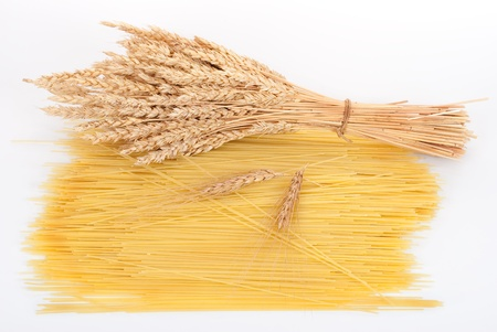 durum: Sheaf of wheat and spilled spaghetti on a gray background