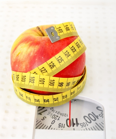 Measuring tape and apple on scales photo