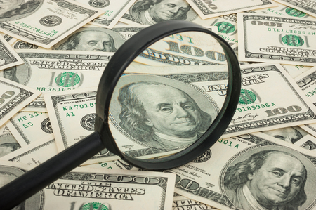 spurious: Hundred dollar banknotes under magnifying glass