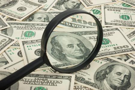 inspected: Hundred dollar banknotes under magnifying glass