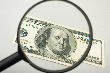 spurious: Hundred dollar bill and magnifying glass