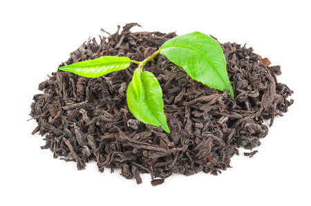Heap of dry black tea with green tea leaves