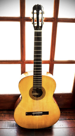 riff: Vintage guitar all scratched and old standing leened at the wooden door
