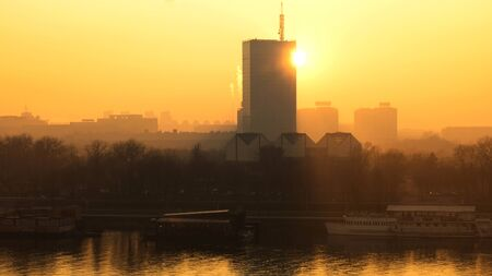 river scape: Sun going behind the building and view of the river Sava and urban scape of Belgrade city