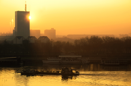 river scape: Sun going behind the building and view of the river Sava with thanker ship and urban scape of Belgrade city