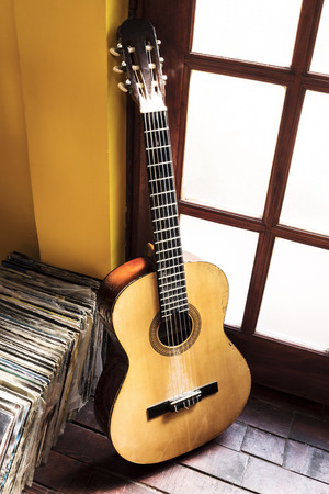 flor: Old dusty guitar and records on the wooden flor