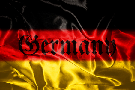 German flag blowing in the wind With Germany Written On It In Gothic Letters Stock Photo
