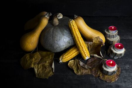 wood carvings: Happy Thanksgiving Day, Decoration on a wooden table with Pumpkins, Corncob, Burning Candles and autumn leaves Stock Photo