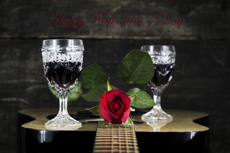 Red Rose And Wine Glasses Resting On Acoustic Guitar With Sign Happy  Valentines Day Photo