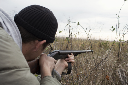Hunter With Old Hunting Riffle Waiting for Pray in the Woods Stock Photo