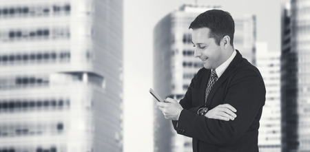 Businessman Holding Phone While Smiling and Feeling Happy With Business City and Corporate Buildings In Background