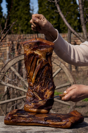 Whole Smoked Bacon Slab Held By Woman's Hand While Being Sliced With Butcher's Knife In A Rustic Environment. Delicious Domestic Food