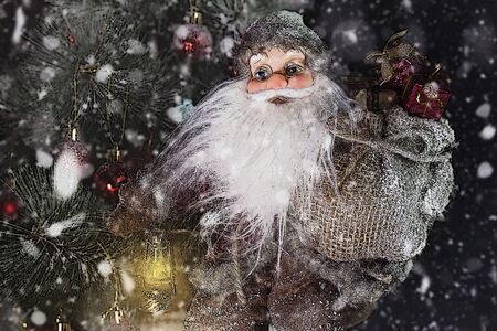 Santa Claus Outdoors Beside Christmas Tree in Snowfall Carrying Gifts to Children. Merry Christmas & New Year's Eve concept