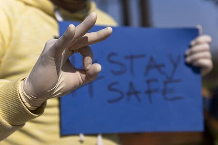Stay safe sign on blue chroma key paper held by a man in surgical gloves giving ok sign with hand Stock Photo