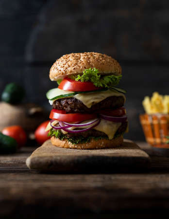 Hamburger with tomatoes, onions, cucumber, lettuce and melting cheese served on a  rustic wooden board with french fries and vegetables in background